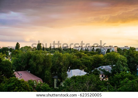 City silhouette during warm sunset. Early evening multicolored summer in Ukraine. Rural landscape with top of the house roofs in morning sunrise with cloudy sky. Urban city skyline at night sky.