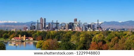 City skyline of Denver Colorado downtown with snowy Rocky Mountains and the City Park Lake. Large panorama.