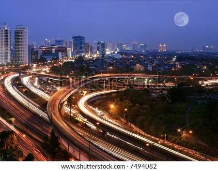 City skyline with multiple flyovers over full moon. Busy traffic light trails.