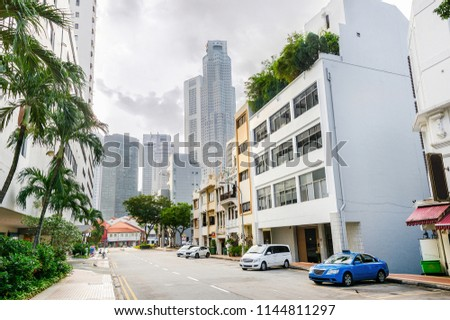 City street of Singapore downtown with parked cars in hazy sunlight