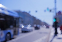 City street with cars and bus. High key blurred image of transport. Unrecognizable cars,faces, bleached effect.Defocused image of the street .sunny day.Background-abstract, graphic design-free