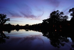 City sunset, lake with trees on the background of a beautiful sky