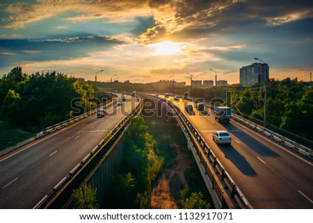 City traffic on asphalt road or highway route at sunset time, lot of cars drive with fast speed, urban transportation cityscape scene
