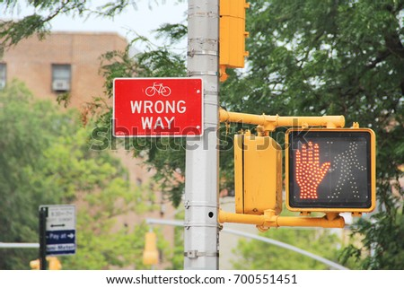 City: Traffic Sign. Wrong Way Red Plate with White Frame at Pedestrian Crosswalk Stop Sign with Buildings and Tree in Background during Daytime. #700551451
