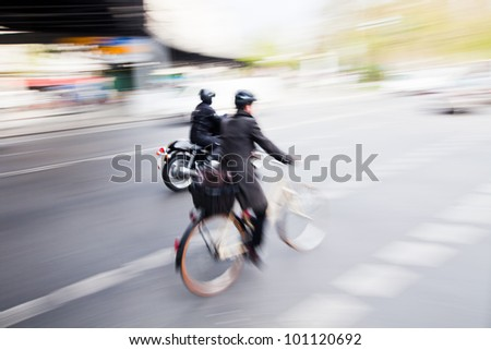 city traffic with a cyclist and a motorcyclist in motion blur