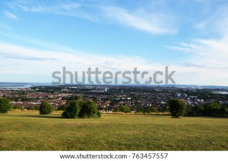 City view from mountain top with partly cloudy sky
