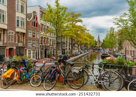 City view of Amsterdam canal and bridge with bikes typical houses church and boats Holland Netherlands