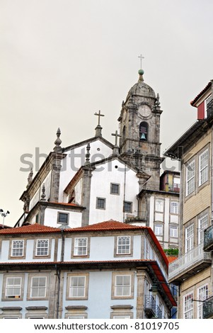 city view of old Porto with historic houses and old church with large bell tower, Portugal