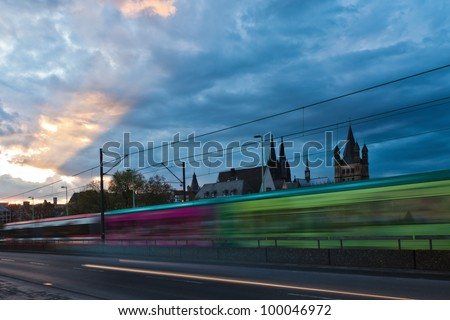 city view with a tram in motion blur and a moody evening sky in Cologne City in Western Germany with the famous Cologne Cathedral in the farther background