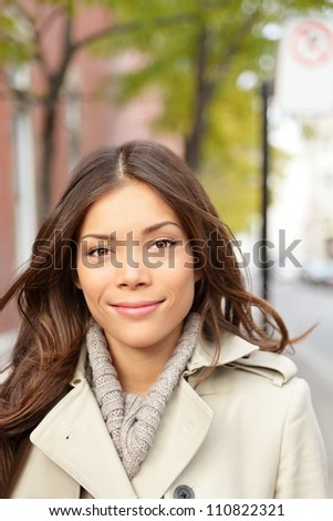 City woman portrait. Young beautiful multiracial woman walking in city wearing trench coat smiling at camera. Mixed race Asian Chinese / Caucasian female model.
