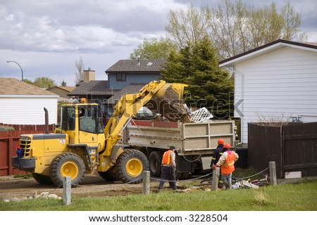City workers cleaning up residential refuse.