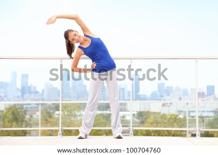 City workout woman stretching after running exercise with skyline in background. Young fitness model training. Mixed race Asian Chinese / Caucasian young woman in Montreal, Quebec, Canada.