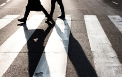 City zebra crossing with two blurry walking pedestrians making long shadows in black and white high contrast
