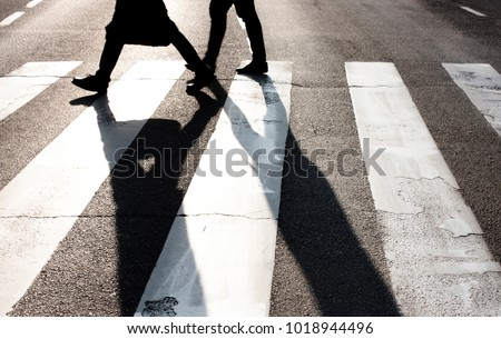 City zebra crossing with two blurry walking pedestrians making long shadows in black and white high contrast - Shutterstock ID 1018944496