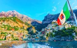 Cityscape and coastal landscape with Italian flag at Positano luxury town on Amalfi Coast and Tyrrhenian Sea in Italy in summer. View of Amalfitana coastline. Vacation and holiday near Salerno.