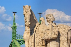 Cityscape - closeup view of the statue of King Saint Stephen against the background of the Liberty Bridge decorated with mythological birds of Turul, on the Gellert Hill in Budapest, Hungary