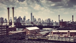 CITYSCAPE FROM BROOKLYN WITH OLD FACTORIES AND CHIMNEYS WITH THE SKYLINE OF NEW YORK CITY AND THE BROOKLYN BRIDGE IN THE BACKGROUND. VINTAGE COLOURS LIKE RED AND BROWN, PANORAMA VIEW ,CLOUDED BLUE SKY