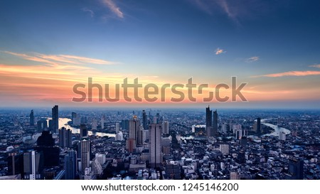 Cityscape in evening sunset from high angle view including modern architechture and Chaophraya River in Bangkok Thailand