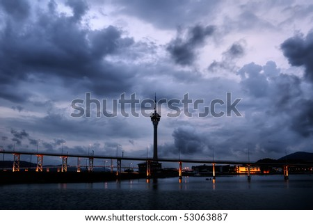 Cityscape in Macao with dramatic clouds and travel tower silhouette in night.