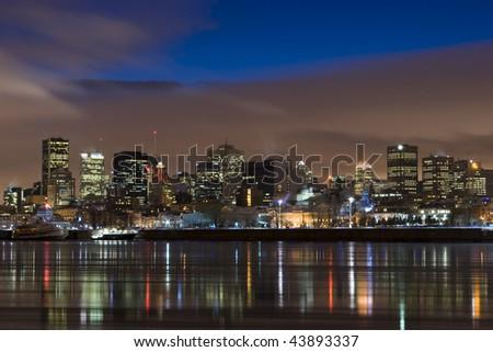 cityscape night scene Montreal Canada over river Saint Lawrence impressive and vibrant dusk sky skyscrapers lights