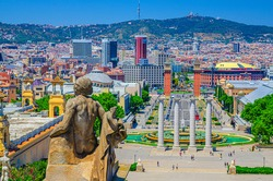 Cityscape of Barcelona with aerial view of Placa d'Espanya or Spain square with Torres Venecianes Venetian towers, Montjuïc fountain and Four Columns Les Quatre Columnes, Tibidabo hill background
