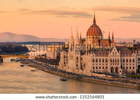 Cityscape of Budapest with bright parliament illuminated by last sunshine before sundown and Danube river with bridge. Pink and purple colors of sky reflecting in water during sunset. #1352564801