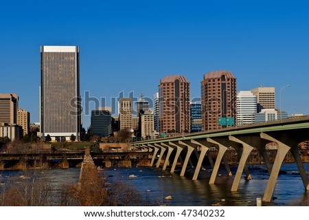 Cityscape of buildings with a bridge leading to the city.  Manchester bridge leading to Richmond, Virginia. - stock photo