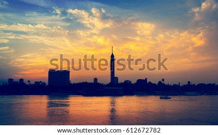 Cityscape of Cairo downtown at sunset with silhouettes of Cairo Tower at horizon. Romantic evening cruise on Nile River - skyline from an embankment of modern Cairo. #612672782