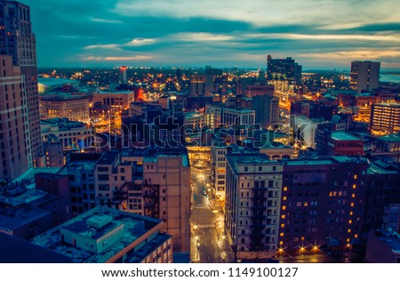 Cityscape of Detroit Michigan glowing at sunrise. Historical architecture, business buildings, apartments, skyscrapers and other structures in foreground. Cloudy blue gray sky with hints of orange. #1149100127
