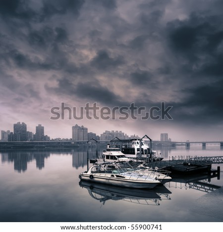 Cityscape of harbor with boat on water against dramatic sky.