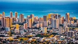 Cityscape of Honolulu city and  Waikiki beach with blue ocean and light reflection from sunset sky to buildings from Ualaka'a lookout on Tantalus mountain  in Honolulu, Oahu, Hawaii USA