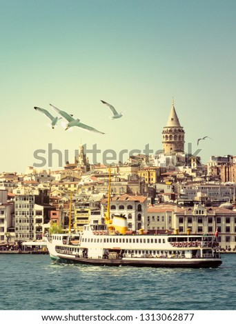 Cityscape of Istanbul with Galata Tower at skyline, steamboat and gulls over the sea. Seaside of Golden Horn at sunset as travel background for your vertical poster or billboard, vintage color tones.