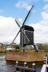 Cityscape of Leiden, the Netherlands. View of New Rhine river and Dutch houses and traditional windmill.