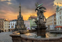 Cityscape of main square with Hercules fountain and monument Holy Trinity Column at sunset sunlight. Olomouc, Czech Republic