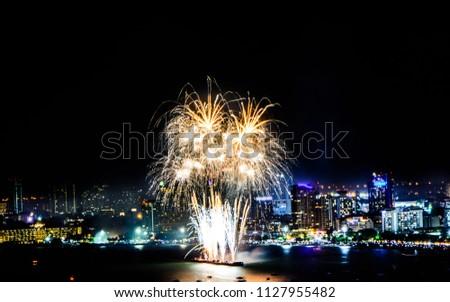 Cityscape of night skyline Pattaya City and Colorful fireworks. Celebration and anniversary concept. Pattaya International Fireworks Festival 2018 at Pattaya beach  on twilight background, Thailand. #1127955482