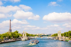Cityscape of Paris, France, with a bateau-mouche cruising on the river Seine, the Alexandre III bridge, the Eiffel tower on the left and the Chaillot palace in the distance by a sunny summer day.