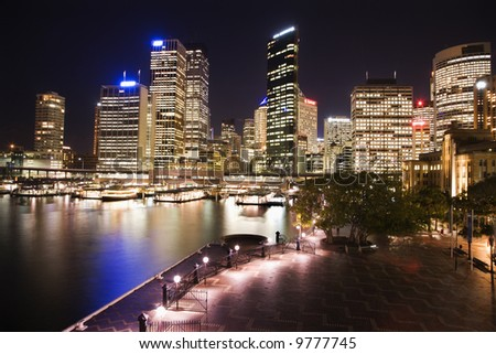 Cityscape of Sydney, Australia with harbor and buildings at night.
