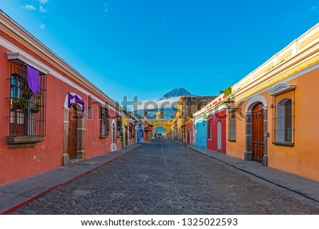Cityscape of the colorful main street of Antigua city at sunrise with the famous yellow arch and the Agua volcano in the background, Guatemala, Central America.