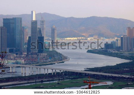 Cityscape of the new downtown in Macau, China. Urban landscape of many various high office buildings and skyscrapers with the giant bridge crossing over islands. #1064612825