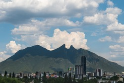 Cityscape panorama of the Cerro de la Silla mountain on a cloudy moody day with blue sky