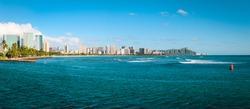 Cityscape panorama of Waikiki Beach shoreline with Diamond Head on Oahu in the distance.