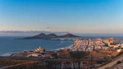 Cityscape. Panoramic view of the city of Las Palmas de Gran Canaria at sunset with Las Canteras beach and La Isleta mountains in the background