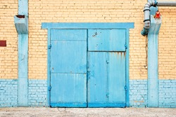 Cityscape. Urban symmetric view of abandoned factory building blue painted rusty gate on yellow brick wall with explosion-proof lantern and copyspace.