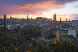 Cityscape view of Edinburgh old town skyline, Princes Street, Balmoral Clock Tower and Edinburgh Castle from Calton Hill with a dramatic sunset in the capital city of Scotland.