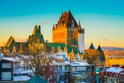 Cityscape view of Quebec City against St Lawrence river and colorful sky at dusk. Skyline scene of old port with snow covered buildings and ground in winter, Quebec, Canada. Building, Outdoor, Travel.