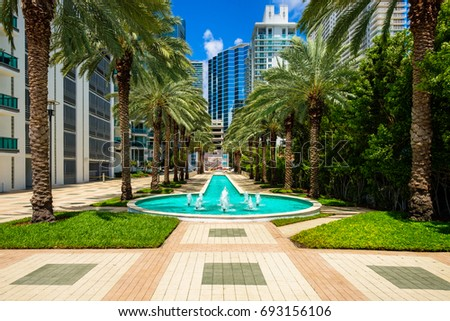 Cityscape view of the Brickell area in downtown Miami with palm trees and skyscrapers.