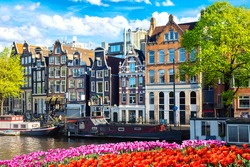 Cityscape view of the canal of Amsterdam in summer with a blue sky, houseboat and traditional old houses. Colorful spring tulips flowerbed on the foreground. Picturesque of Amsterdam, The Netherlands