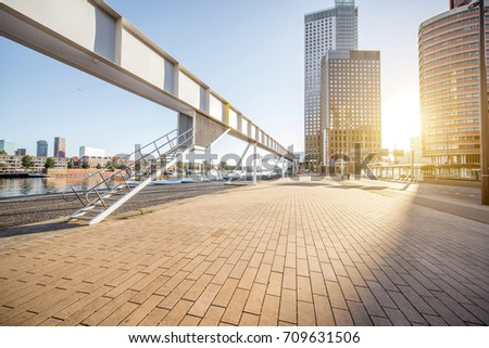 Cityscape view with the modern footbridge and skyscrapers during the morning in Rotterdam