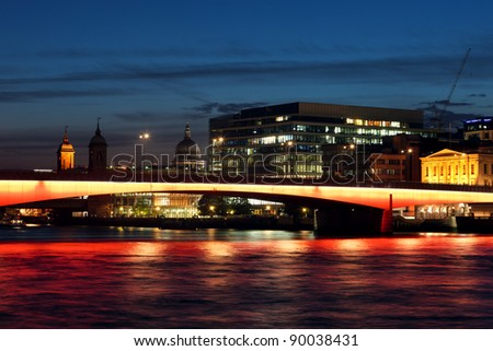 Cityscape with illuminated London Bridge at night.
