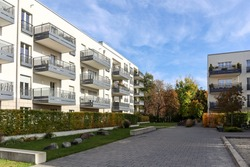 Cityscape with modern residential area, new apartment buildings and green courtyard with pedestrian walkway and trees in autumn